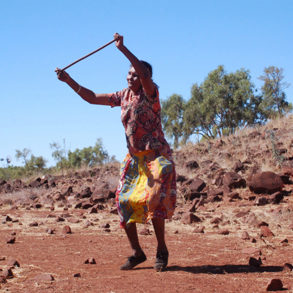 Pauline Ryan Namija dancing near women's stone shelters, Jinparrak (Old Wave Hill Station), 26 August 2014