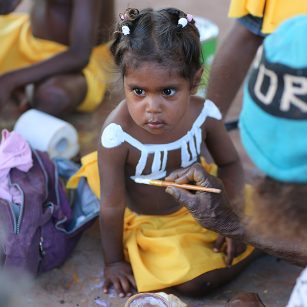 Little girl being painted up by Violet Wadrill Nanaku for Wajarra, Karungkarni Art and Culture Aboriginal Corporation, 20 October 2015